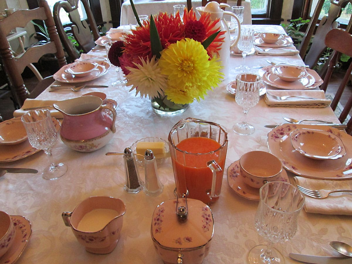 Dining room table setting with china, a bowl of fruit, and baked goods