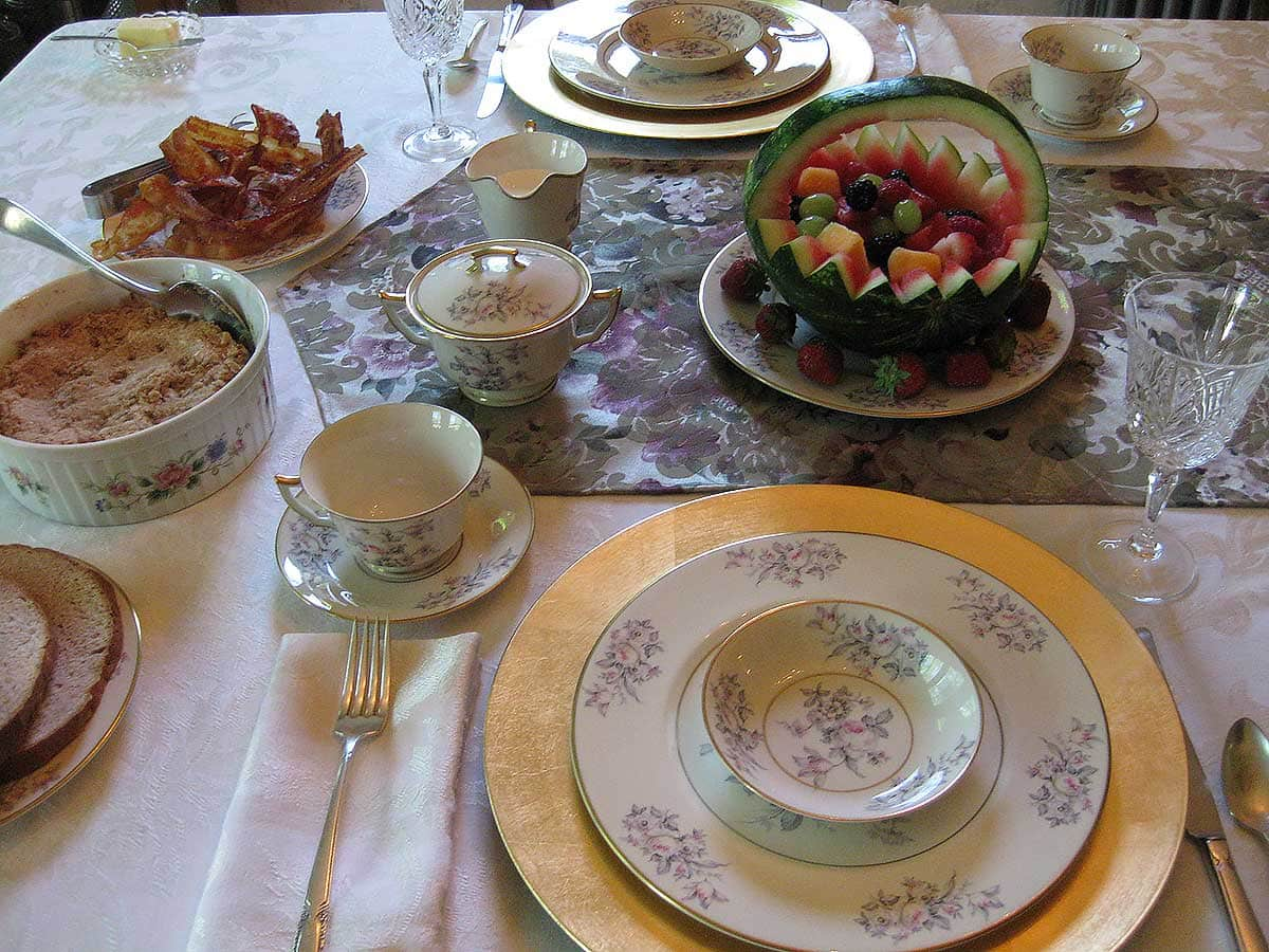 Dining room table setting with carved watermelon basket full of fresh fruit and other food