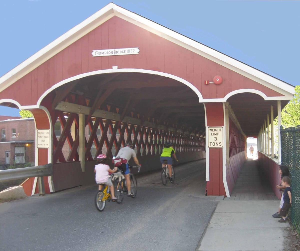 Thompson Covered Bridge with bicyclists riding through and two little children on the side watching