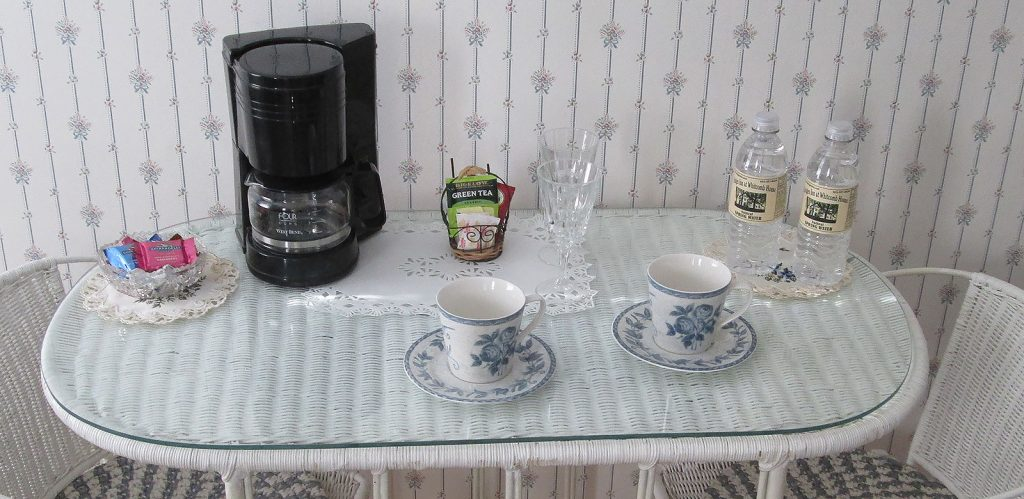 Wicker table with coffee maker, tea cups, bottled water, and a bowl of chocolates