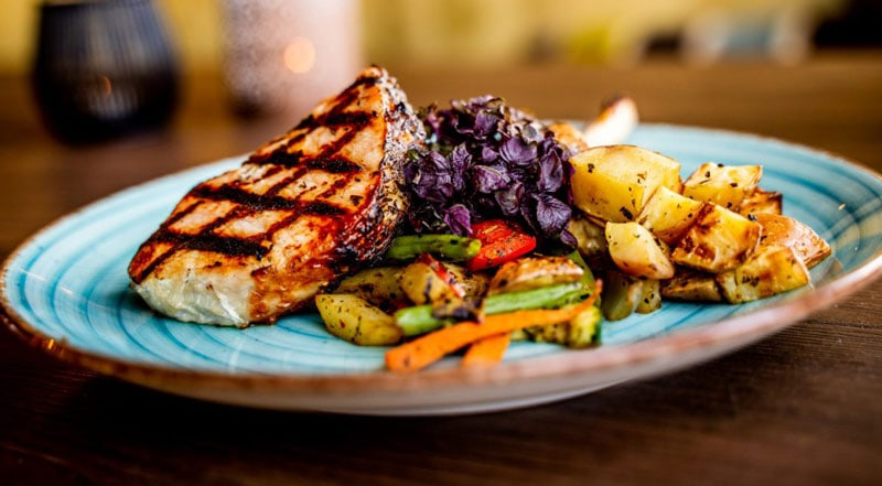 Delicious looking meal on a plate with grilled chicken, vegetables and more
